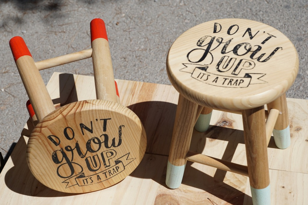"""stools with writing on them: """"Don't grow up it's a trap"""""""